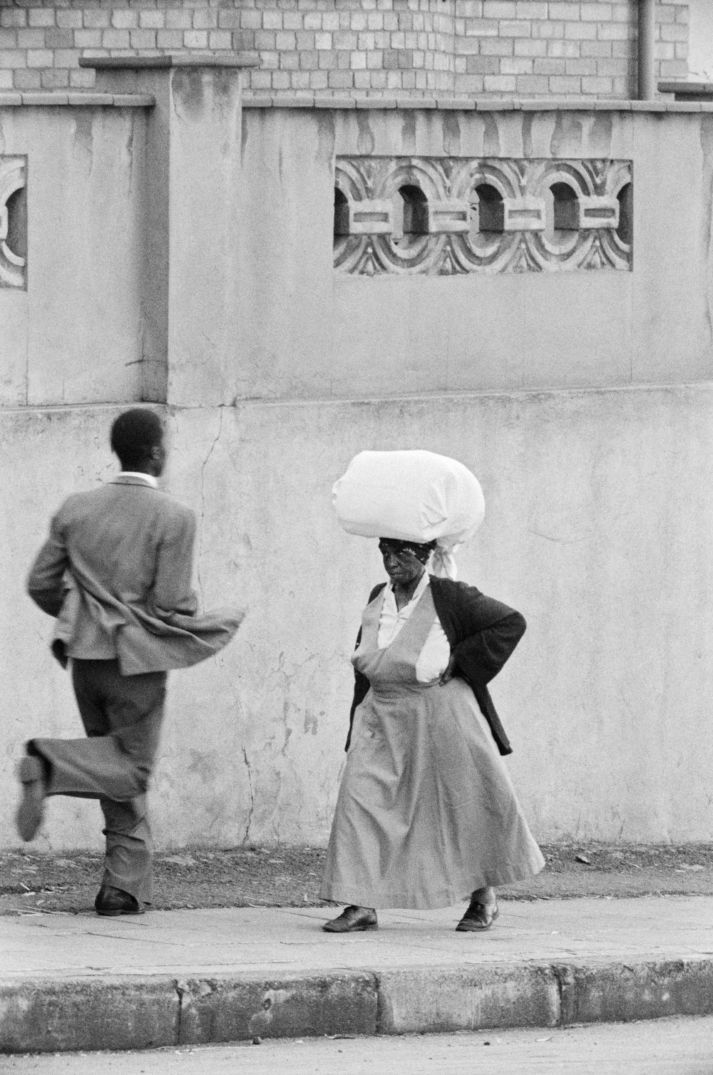 Anna Lebako, a washerwoman from Soweto carrying the week's laundry to a white suburban family, Harrow Road, 1961