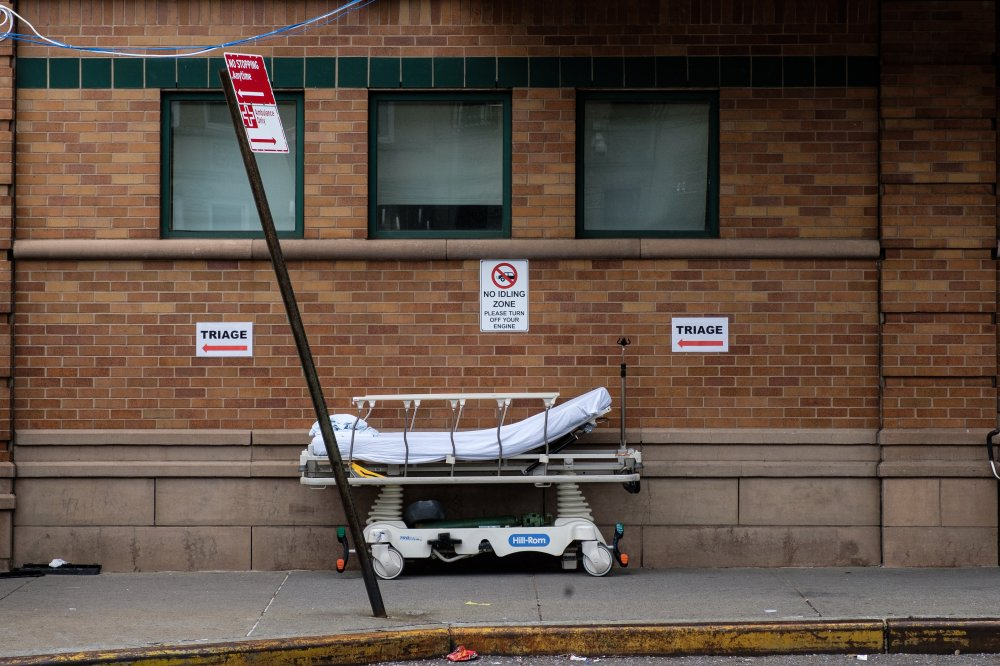 """An empty bed placed outside of Maimonides Medical Center with the sign of """"TRIAGE"""""""